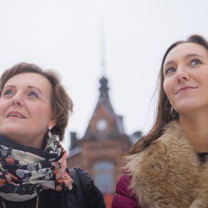 Pirjo ja Saija Viherlaakso seisovat ulkona, katsovat yläviistoon hymyillen.