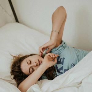 Nainen venyttelee sängyssä käsiään.