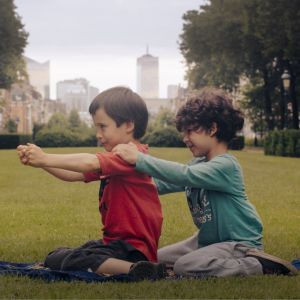 Aatos ja Amine puistossa, leikkimässä lentävällä matolla. Reetta Huhtasen dokumenttielokuvasta.