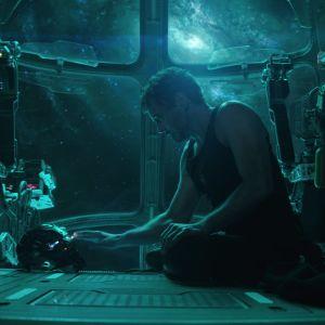 Iron Man sitter på golvet i en rymdfakost och tittar på sin hjälm.