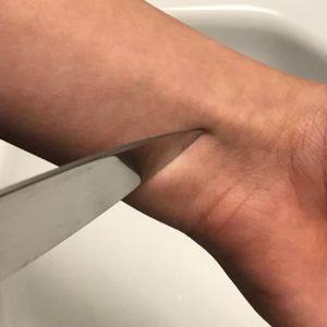 En knivspets mot en handled.