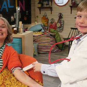 BUU-klubbens programledare Malin blir undersökt av barngästen Malte då de leker sjukhus i BUU-klubben