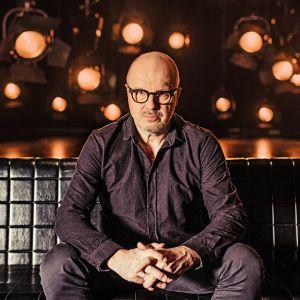 Toimittaja J.P. Pulkkinen istuu sohvalla ja katsoo tiukasti kameraan. Kuva on otettu Tleveision tiiliskivet -sarjaa varten.