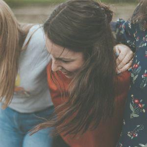Artikkelikuva Abitreenien artikkeliin. Kuvassa kolme nuorta naista nojaa toisiinsa ja nauraa.