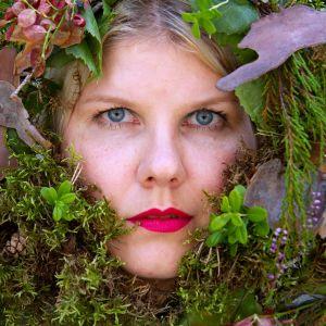 Sari Casalin kasvot sammalten ja varpujen keskellä.