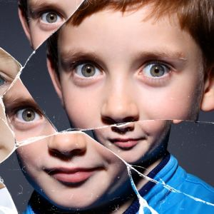 Två barn syns i en krossad spegel