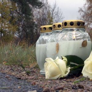 Kynttilöitä ja ruusu onnettomuuspaikalla tien varressa.