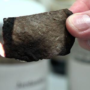 En man håller en brinnande bit oljeskiffer i handen.