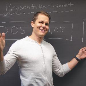 Matematiikan opettaja Ville Aitlahti luokan taulun edessä