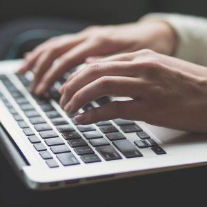 Kädet kirjoittavat kannettavalla tietokoneella