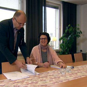 man och kvinna tittar i papper