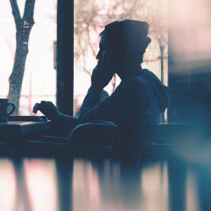Mies istuu kahvilassa tietokoneen ääressä