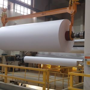 Suurta paperirullaa siirretään paperitehtaalla.