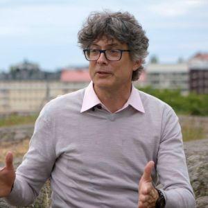 Per Espen Stoknes sitter på en klippa och berättar