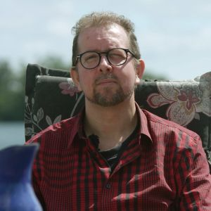 Henrik Kniberg sitter i en stol vid vattnet.