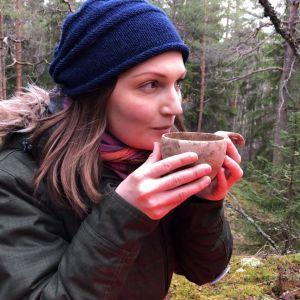 Tutkija Tytti Pasanen juo metsässä teetä kuksasta.