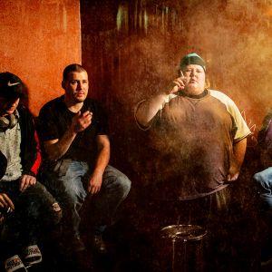 Viisi ihmistä istuu puolikaaressa, osa polttaa tupakkaa, tunnelma on hämyinen.