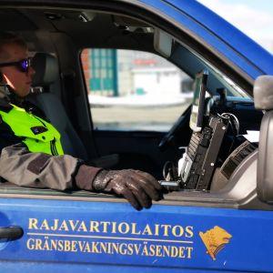 """En man sitter i en bil med texten """"Gränsbevakningsväsendet""""."""