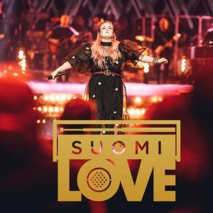Nainen seisoo kädet levällään lavalla. Kuvan päällä poltettu SuomiLOVEn logo.
