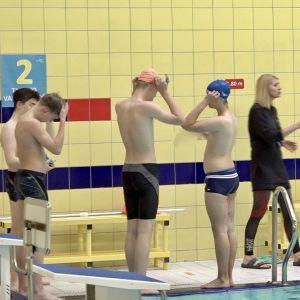 Litauiska barn förbereder sig för simundervisning vid bassängkanten.