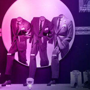 mustavalkoinen, väritetty kuva näyteikkunasta, jossa miesten pukuja ja paitoja