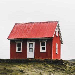 Punainen mökki autiossa maisemassa.