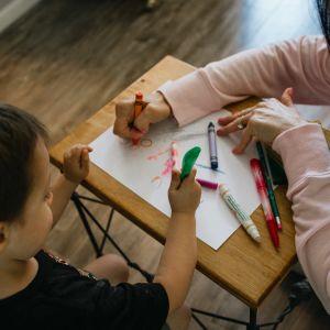 Lapsi piirtää aikuisen kanssa.