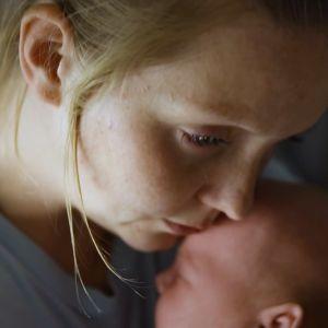 Väsynyt äiti halaa vauvaansa.