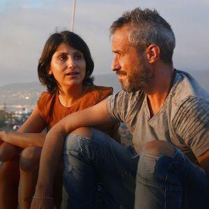 Mies ja nainen kalliolla, taustalla avautuu kaupunki