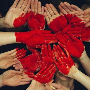 Käsiä, joihin maalattu punainen sydän.