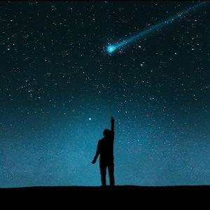 Ihmisen siluetti tähtitaivaan edessä.
