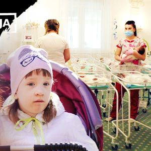 Lapsi istuu rattaissa, taustalla vauvoja pienissä sängyissä ja hoitajien sylissä.