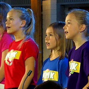 Barn i färgglada t-skjortor sjunger i kör.