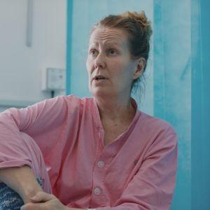 Ursula Vasama koronaosastolla, istuu sairaala vuoteella