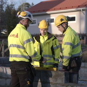 Tre unga män står tillsammans i gula kläder och hjälmar den ena håller en motorsåg