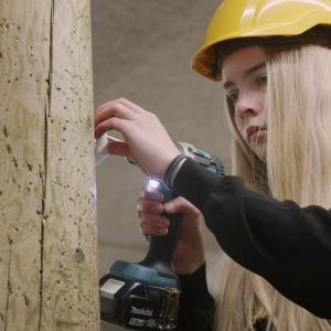 Ung kvinna i förd gul skyddshjälm håller i en elektrisk borr och borrar i en kraftig trästolpe med fokuserad blick.