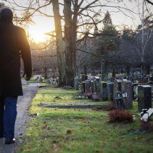 Mies kävelee kohti laskevaa aurinkoa hautausmaalla