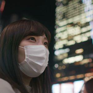 Nainen katsoo kameraan ohi maski kasvoillaan.