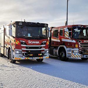 Brandbilar på rad i vintrigt landskap.