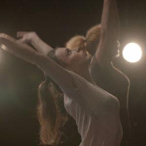 Naistanssijat lavalla kurottautuvat ylöspäin valonheittimiä vasten. Kuva dokumentista Tanssien vapauteen