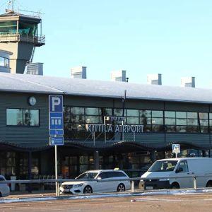 Valkoisia taksiautoja seisoo Kittilän lentoaseman pihalla talvisessa maisemassa.