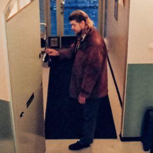 Mies seisoo rappukäytävässä ja kurkottaa avautuvaan ulko-oveen.
