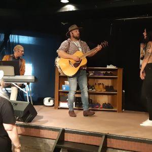 Kranniteatterin Anne Angeria seuraa näytelmän kohtausta, jossa Tuomas Heinikoski soittaa kitaraa ja laulaa.