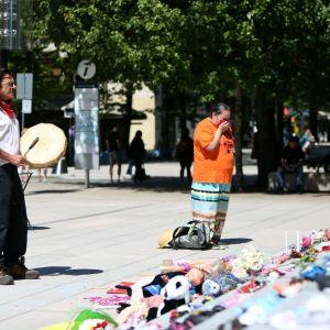 Sörjande människor hedrar minnet av 215 barn som hittas i en massgrav.  Ceremoni utanför Vancouver Art Gallery där 215 par barnskor ställts ut.