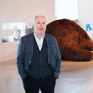 Cgefen för Estlands nationalmuseum Alar Karis står i en utställningshall framför en stor liggande björninstallation..
