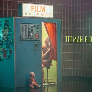 Nainen istuu valokuvauskopissa ja katsoo punaisen verhon raosta ulkopuolella istuvaa vauvaa. Kuvan päällä teksti Teeman elokuvafestivaali 2021.