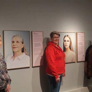Hoitoalan ammattilaiset Jonna Pakisjärvi, Miia Alasaarela ja Sari Soini seisovat Kemin historiallisessa museossa tutustumassa hoitoalan arkea kuvaavaan näyttelyyn.