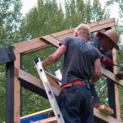Jim och Johan spikar fästen för fasadbräder.