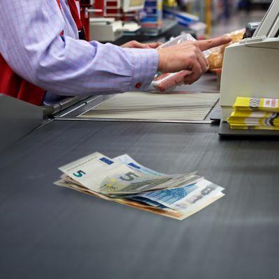 Nippu seteleitä kaupan kassan hihnalla.