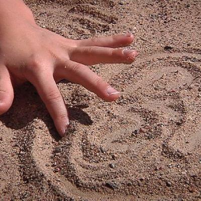 Lapsen sormi piirtää hiekkaan kuvioita. Koulujännitys voi saada lapsen haikailemaan kesäloman huolettomia päiviä.